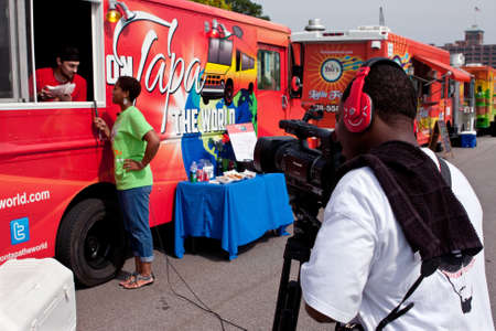 documenting: Atlanta, GA, USA - August 3, 2013:  A cameraman shoots a reporter interviewing a food truck employee at the Cool Dads Rock Soap Box Derby, at the Old 4th Ward Park in Atlanta.  The event was free and open to the public.