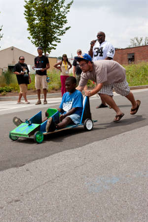 Atlanta, GA, USA - August 3, 2013:  A man pushes a kid steering a toy car down a hilly street in the Cool Dads Rock Soap Box Derby, at the Old 4th Ward Park in Atlanta.  The event was free and open to the public.