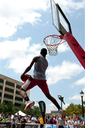 Athens, GA, USA - August 24, 2013:  A young man jumps high attempting a reverse dunk in the slam dunk competition of a 3-on-3 basketball tournament held in the streets of downtown Athens. Editorial