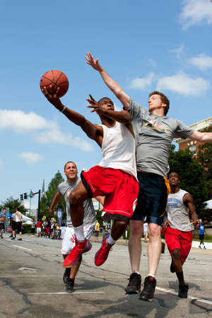 Athens, GA, USA - August 24, 2013:  A young man jumps to get off a shot against a defender, in a 3-on-3 basketball tournament held on the streets of downtown Athens.