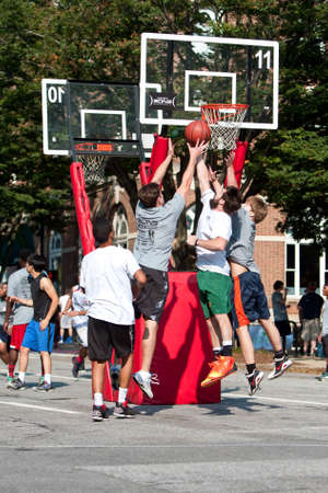 basketball team: Athens, GA, USA - August 24, 2013:  Three men jump battling for the ball in a 3-on-3 basketball tournament held on the streets of downtown Athens. Editorial