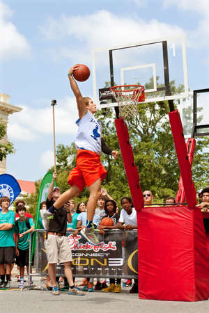 Athens, GA, USA - August 24, 2013:  A young man elevates above the rim to dunk a basketball in the slam dunk competition of a 3-on-3 basketball tournament held in the streets of downtown Athens.