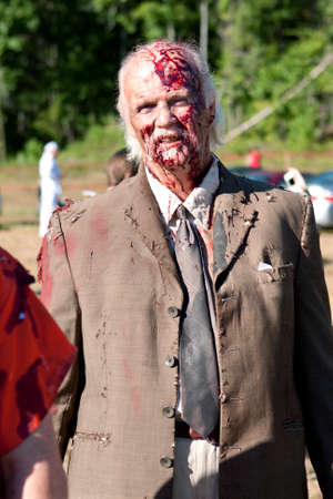 Dalton, GA, USA - September 14, 2013:  A bloody elderly male zombie gets ready to take the field to menace runners in the Run For Your Lives 5K event.  The event was free to spectators.