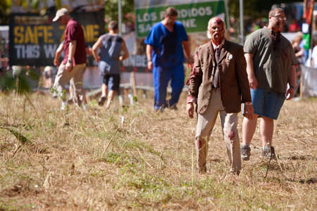 Dalton, GA, USA - September 14, 2013:  An elderly male zombie wearing bloody coat and tie, menacingly stalks runners in the Run For Your Lives 5K event.  The event was free to spectators. Publikacyjne