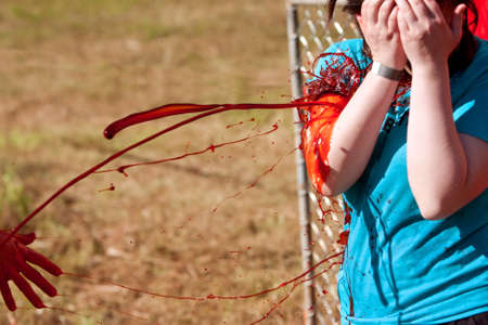 Dalton, GA, USA - September 14, 2013:  A woman gets fake blood splattered on her so she can menace runners as a zombie in the Run For Your Lives 5K event.  The event was free to spectators.