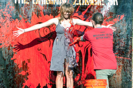 Dalton, GA, USA - September 14, 2013:  A woman zombie dressed in a torn dress gets fake blood splattered on her so she can menace runners in the Run For Your Lives 5K event.  The event was free to spectators.