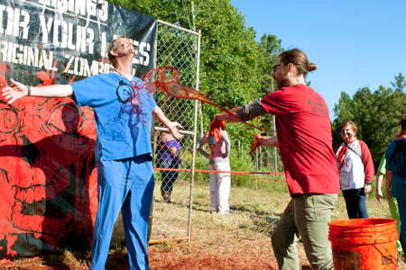 gory: Dalton, GA, USA - September 14, 2013:  A man dressed in medical scrubs gets fake blood splattered on him so he can menace runners in the Run For Your Lives 5K event.  The event was free to spectators. Editorial