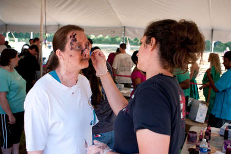 Dalton, GA, USA - September 14, 2013:  A woman gets zombie makeup applied as she prepares to chase people running in the Run For Your Lives 5K event.  The event was free to spectators.