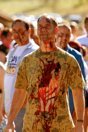 Dalton, GA, USA - September 14, 2013:  A male zombie waits in line to be splashed with fake blood so he can terrorize runners in the Run For Your Lives 5K event.  The event was free to spectators.