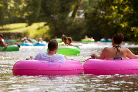 Helen, GA, USA - August 24, 2013:  A couple enjoys tubing down the Chattahoochee River with hundreds of others in North Georgia on a warm summer afternoon.