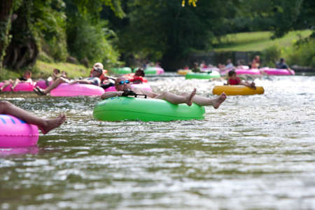Helen, GA, USA - August 24, 2013:  Dozens of people enjoy tubing down the Chattahoochee River in North Georgia on a warm summer afternoon.
