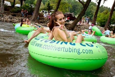 Helen, GA, USA - August 24, 2013:  A teenage girl flashes a peace sign as she tubes down the Chattahoochee River in North Georgia on a warm summer afternoon. Editorial