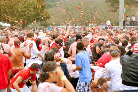 food fight: Conyers, GA, USA - October 19, 2013:  Crowd of people throws tomatoes at each other in a massive Tomato Royale food fight at the Great Bull Run.