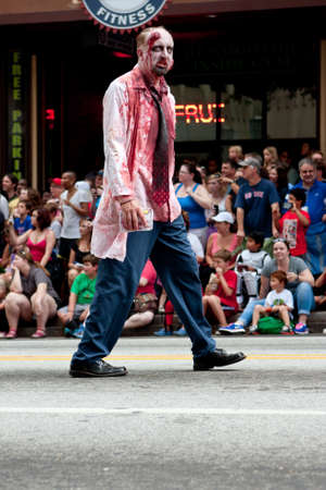 gruesome: Atlanta, GA, USA - August 31, 2013:  A bloody zombie doctor menaces the crowd watching the Dragon Con parade pass by on Peachtree Street. Editorial