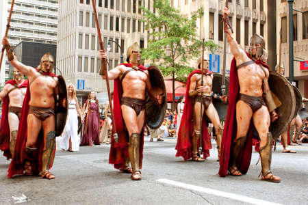 Atlanta, GA, USA - August 31, 2013:  Several men representing Spartan warriors from the movie 300 salute the crowd while walking in the annual Dragon Con parade.
