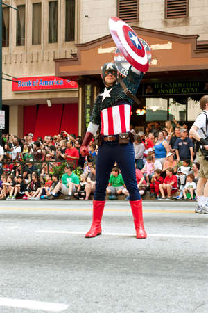 Atlanta, GA, USA - August 31, 2013:  Super hero Captain America raises his shield to salute the crowd at the annual Dragon Con parade on Peachtree Street.
