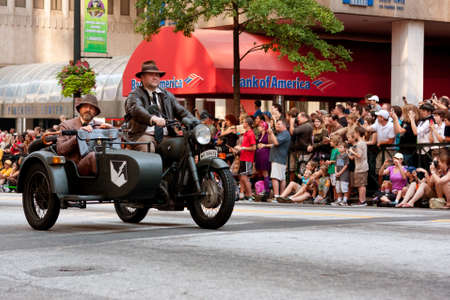 jones: Atlanta, GA, USA - August 31, 2013:  Two men dressed like characters from the Indiana Jones movies, ride a motorcycle down Peachtree Street in the annual Dragon Con parade. Editorial