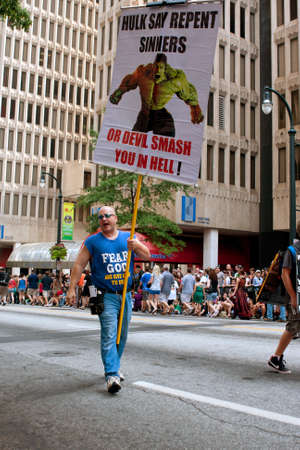 repent: Atlanta, GA, USA - August 31, 2013:  A man carrying a sign showing the incredible hulk, urges spectators at the Dragon Con parade in Atlanta to repent of their sins.