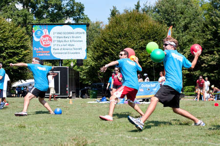 dodge: Atlanta, GA, USA - September 7, 2013:  Three young men simultaneously wind up to throw balls during a dodge ball game at A Day For Kids, an event where adults play kids games to beneft the Girls and Boys Clubs of America.