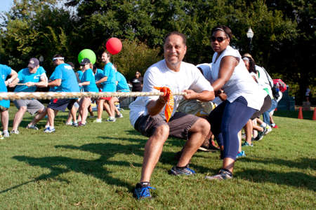 Atlanta, GA, USA - September 7, 2013:  Two teams pull hard in the tug-of-war competition at A Day For Kids, an event where adults play kids games to beneft the Girls and Boys Clubs of America.