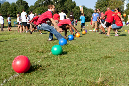 Atlanta, GA, USA - September 7, 2013:  Two teams sprint to grab balls to start a dodge ball game in A Day For Kids, an event where adults play kids games to beneft the Girls and Boys Clubs of America. Editorial