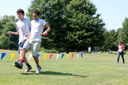 Atlanta, GA, USA - September 7, 2013:  Two young men compete in the three-legged race at A Day For Kids, an event where adults play kids games to beneft the Girls and Boys Clubs of America.