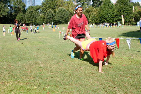 Atlanta, GA, USA - September 7, 2013:  Two young women compete in the wheelbarrow race at A Day For Kids, an event where adults play kids games to beneft the Girls and Boys Clubs of America. 新聞圖片