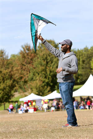 airborn: Atlanta, GA, USA - October 26, 2013:  A man holds a kite high to get it airborn, at the World Kite Festival in Piedmont Park.