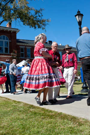 square dancing: Lawrenceville, GA, USA - October 12, 2013:  A senior citizen couple square dances outdoors at the Old Fashioned Picnic and Bluegrass Festival.  The event was free to the public. Editorial