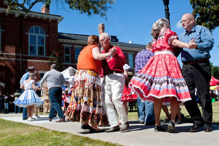square dancing: Lawrenceville, GA, USA - October 12, 2013:  Senior citizens square dance outdoors at the Old Fashioned Picnic and Bluegrass Festival.  The event was free to the public.