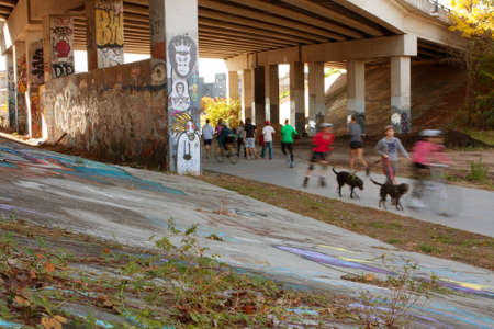 urban redevelopment: Atlanta, GA, USA - November 2, 2013:  Motion blur of several people exercising along a graffiti covered trail that is part of the Atlanta Beltline, a 22-mile long urban redevelopment project for the city of Atlanta that will eventually connect 45 intown n