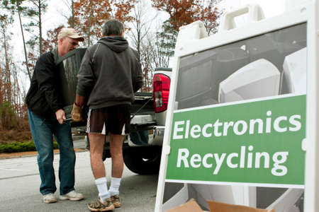 Lawrenceville, GA, USA - November 23, 2013:  Two men carry a discarded television set past an Electronics Recycling sign at Gwinnett Countys America Recycles Day event.