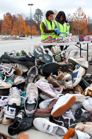 Lawrenceville, GA, USA - November 23, 2013:  Two female teen volunteers sort through tennis shoes before tossing them into a pile of sneakers to be recycled, at Gwinnett Countys America Recycles Day event.