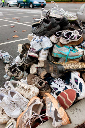 Lawrenceville, GA, USA - November 23, 2013:  Tennis shoes sit piled high in a parking lot as part of Gwinnett Countys America Recycles Day event.  Hundreds of people dropped off items for recycling.