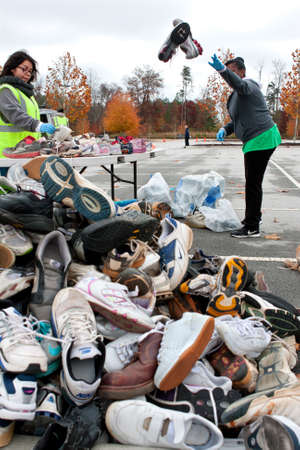 Lawrenceville, GA, USA - November 23, 2013:  Volunteers sort and toss sneakers into a large pile of shoes at Gwinnett Countys America Recycles Day event.