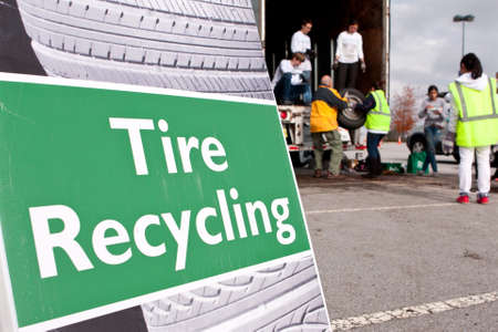 Lawrenceville, GA, USA - November 23, 2013:  Teen volunteers help a man put old worn tires to be recycled onto a truck at Gwinnett County's America Recycles Day event.