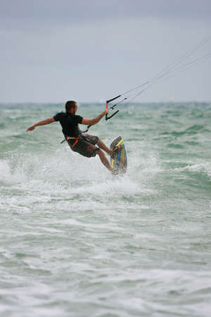 Ft. Lauderdale, FL, USA - December 28, 2013:  A man rides the waves while parasail surfing off the coast of Ft. Lauderdale over the Christmas holidays. Editoriali