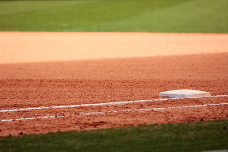 First base is featured in empty baseball field, showing infield dirt and outfield grass  Stock Photo