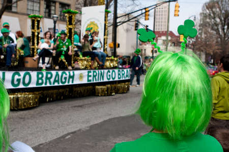 onlooker: Atlanta, GA, USA - March 15, 2014   A woman wearing a green wig watches a parade float go by in the annual Atlanta St  Patrick s parade