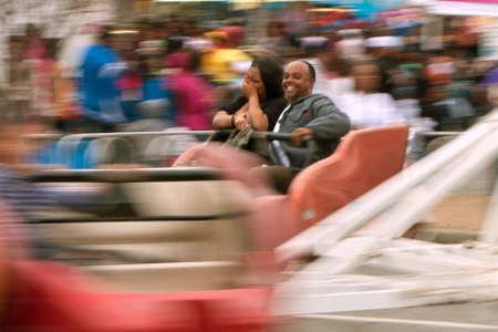 adrenaline rush: Atlanta, GA, USA - March 15, 2014:  A couple laughs while riding a fast-moving carnival ride at the annual Atlanta Fair.
