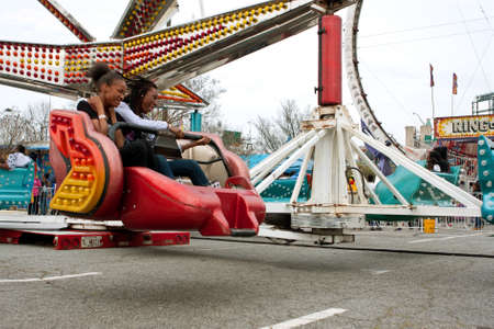 scrambler: Atlanta, GA, USA - March 15, 2014:  Two teens enjoy riding a fast-moving carnival ride at the annual Atlanta Fair.