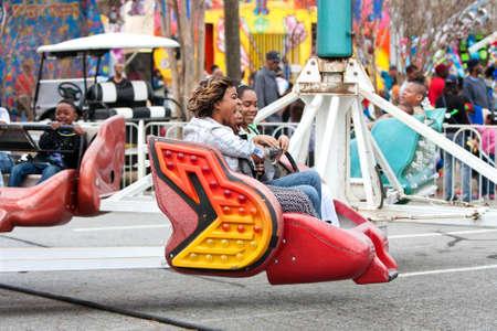 scrambler: Atlanta, GA, USA - March 15, 2014:  Women laugh while riding a fast-moving carnival ride at the annual Atlanta Fair.