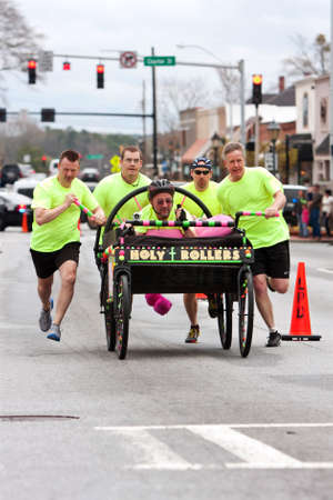 eclectic: Lawrenceville, GA, USA - March 29, 2014:  A team of clergymen pushes a Holy Rollers bed down a street in the annual Lawrenceville Bed Race, to benefit a local Gwinnett County homeless shelter.