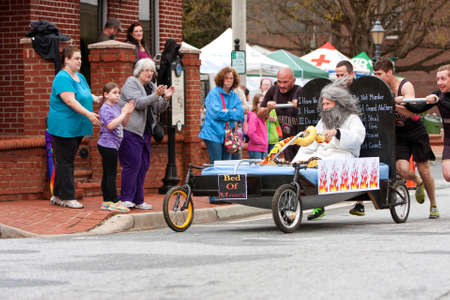 Lawrenceville, GA, USA - March 29, 2014:  A team pushes the bed of Moses around a corner in the annual Lawrenceville Bed Race, to benefit a local Gwinnett County homeless shelter.
