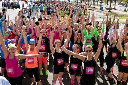 adrenaline rush: Atlanta, GA, USA - April 5, 2014   A throng of excited runners gathered at start line, jubilantly waves to camera at the Ridiculous Obstacle Challenge  ROC  5k race   Editorial