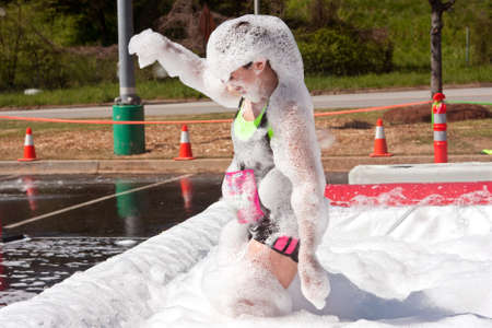 adrenaline rush: Atlanta, GA USA - April 5, 2014   A young woman emerges from the foam pit covered head to toe in bubbles, at   the Ridiculous Obstacle Challenge  ROC  5k race