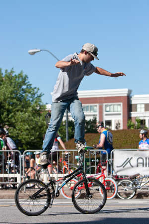 flatland: Athens, GA, USA - April 26, 2014:  A young man practices his flatland tricks before the start of the BMX Trans Jam competition on the streets of downtown Athens. Editorial