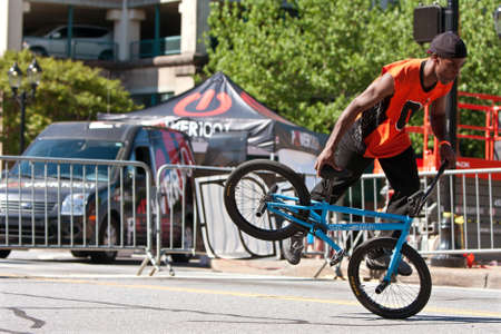 flatland: Athens, GA, USA - April 26, 2014:  A young male practices his flatland tricks before the start of the BMX Trans Jam competition on the streets of downtown Athens.