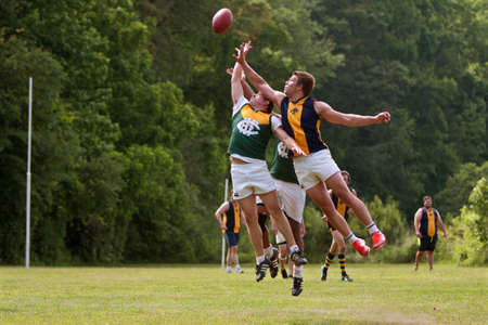 Roswell, GA, USA - May 17, 2014:  Players jump and compete for the ball in an amateur club game of Australian Rules Football in a Roswell city park.