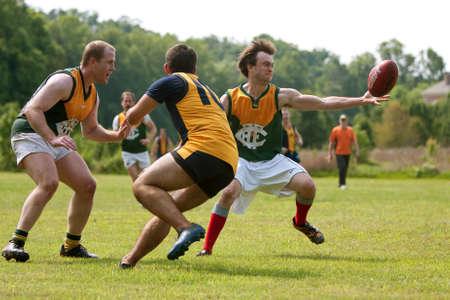 Roswell, GA, Verenigde Staten - 17 mei 2014: Een speler bereikt om de bal op de vlucht te vangen in een amateur club spel van Australian Rules Football in een Roswell stadspark.